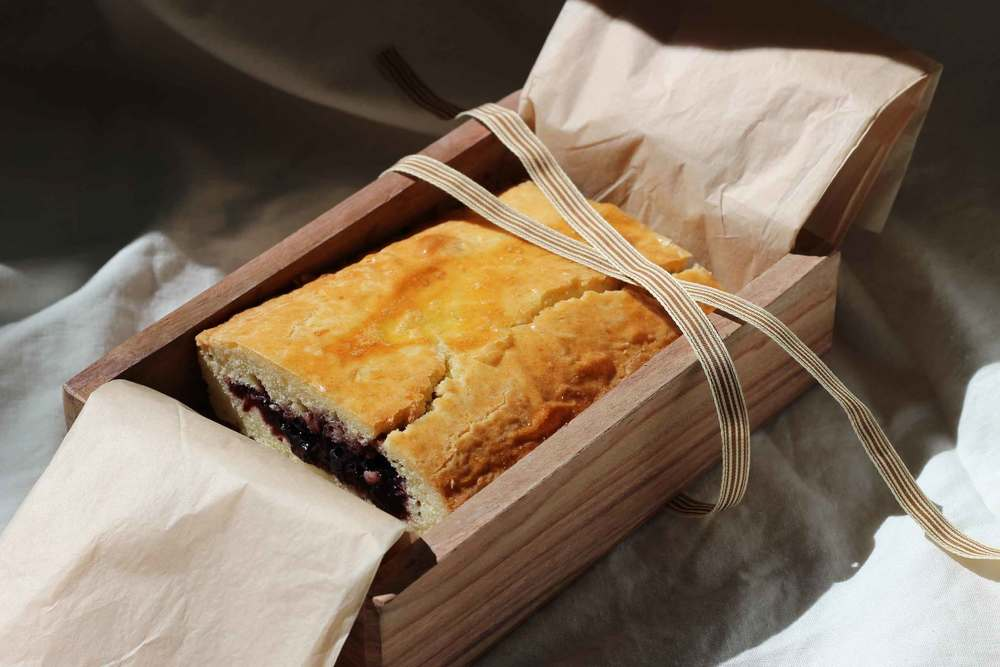 A homemade gateau basque in a tissue-lined wood box, wrapped with a ribbon.  A perfectly thoughtful gift.  Recipe at ThreadandWhisk.com.