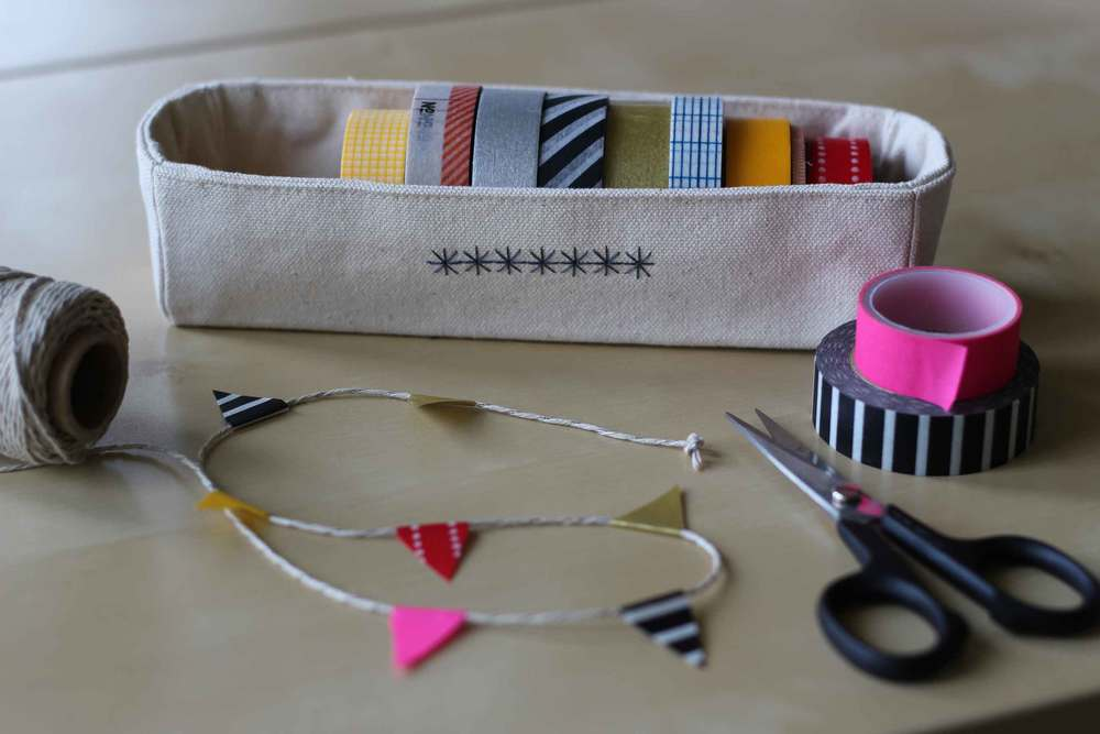 A simple sewn box to hold our washi tape rolls.  Washi tape flag garland.  Thread & Whisk.