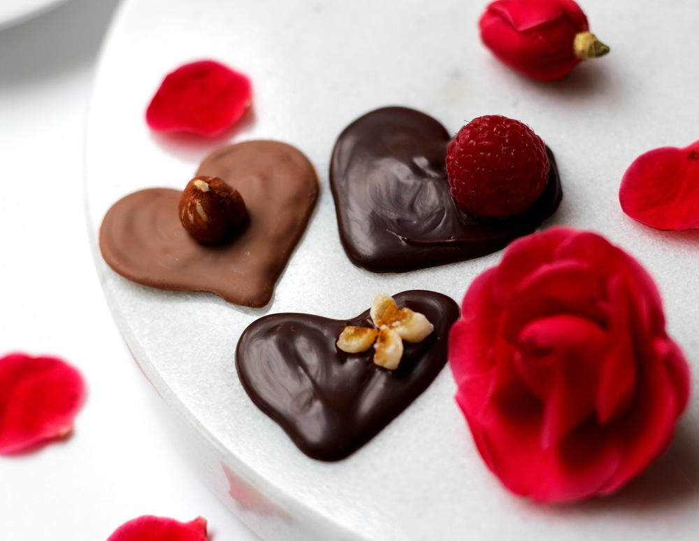 Dark and milk chocolate hearts with nuts and berries on top.  Surrounded with rose petals on a dessert pedestal, ready for a Valentine celebration.  Call them les petites gourmandises. Recipe at ThreadandWhisk.com