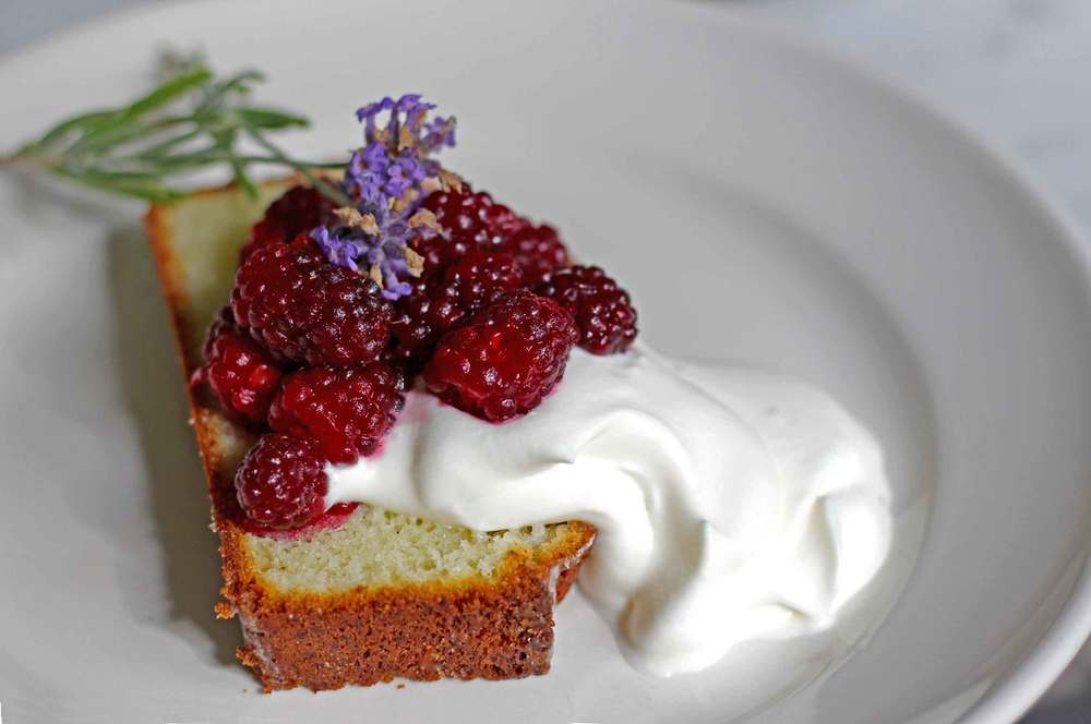 Slice of lavender pound cake, with tayberries and whipped cream, beautiful summer season recipe at Thread & Whisk