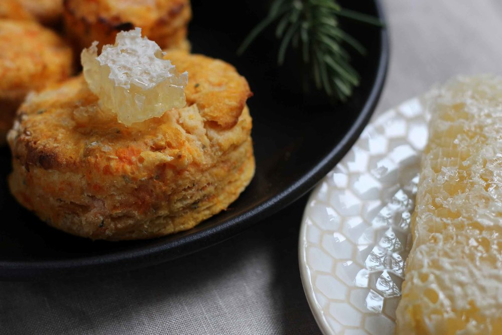 A plate of warm sweet potato and rosemary biscuits with a chunk of delicious comb honey on top.