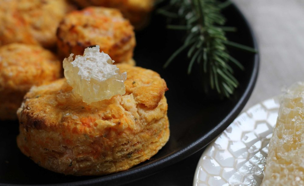 Plate of sweet potato and rosemary biscuits topped with a bit of comb honey.