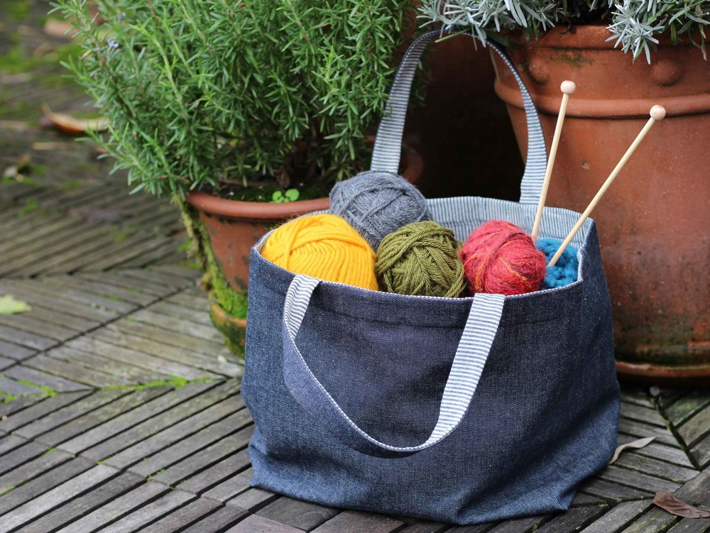 Our handmade denim tote, filled with colorful yarn balls and some knitting needles, sitting in the garden waiting to be made into something special.  Find the simple reversible tote bag instructions on ThreadandWhisk.com