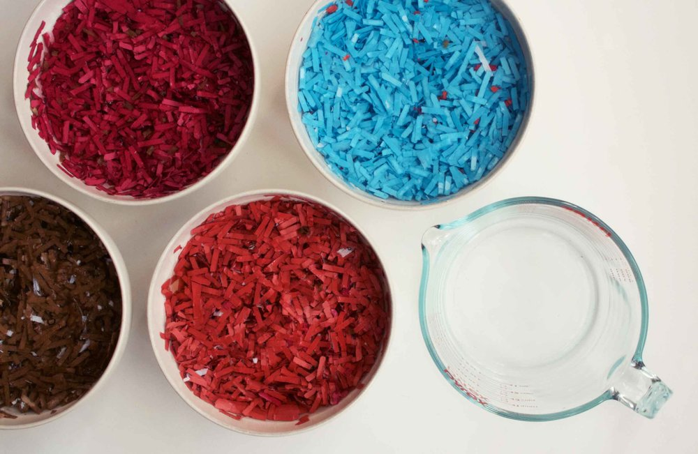 Colorful shredded papers, soaking in water to be turned back into pulp. Wildflower seeds will be added to the pulp, which will be formed into seed pebbles, also commonly known as seed bombs.