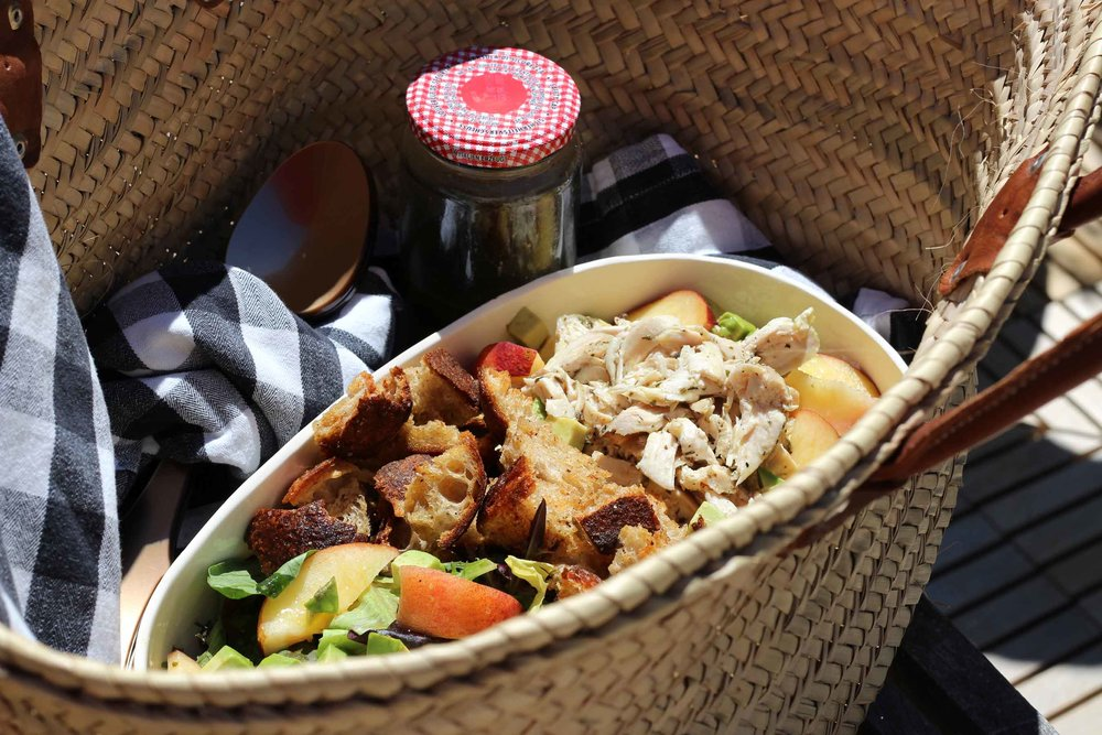 The picnic basket is packed and ready to rumble.  Salad ingredients - shredded chicken, slice peaches and avocado, and freshly made croutons  - are arranged and ready in the bowl. The freshly whirled basil lime vinaigrette is ready to be tossed in and enjoyed.