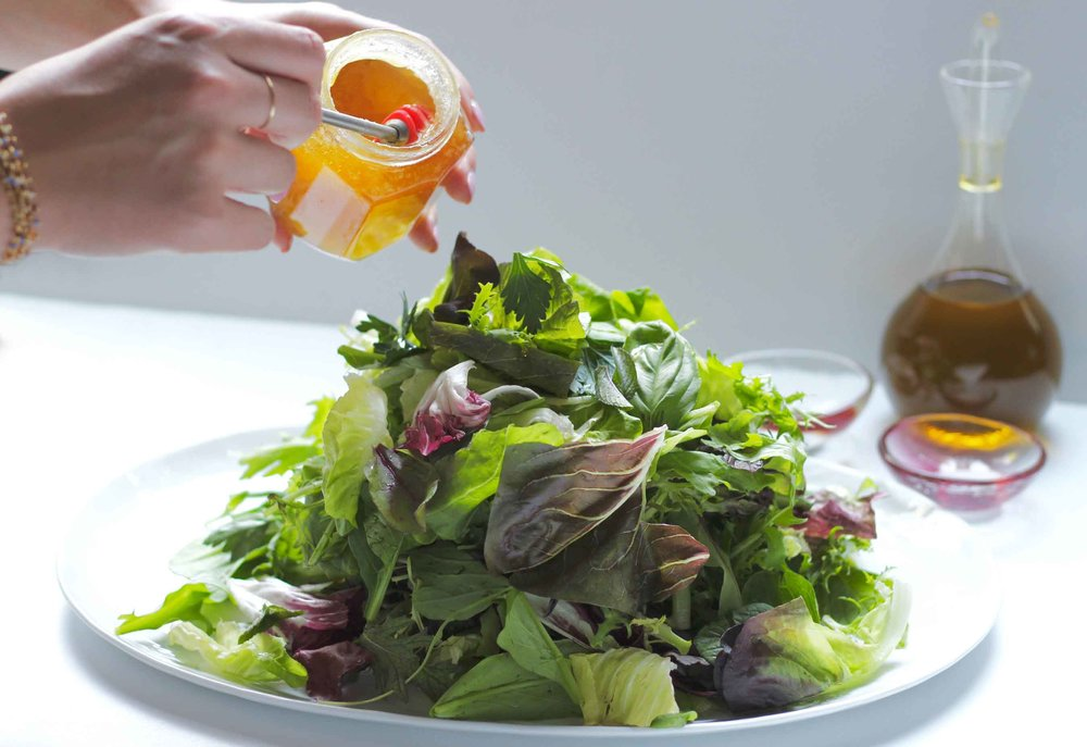 Drizzling ribbons of honey over our mixed greens and herbs salad.