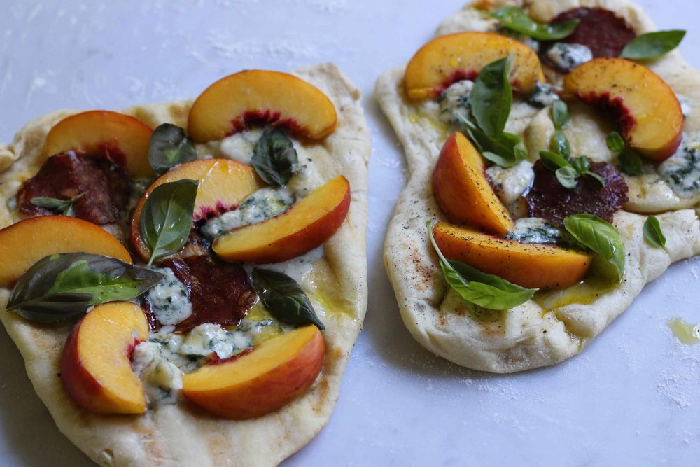Two mini pizzas topped with fresh peach, blue cheese, spicy salami, and basil, fresh off the grill.  Super easy summer option for a lunch or dinner.  Make your own crust in 5 minutes.  Find this recipe at ThreadandWhisk.com.