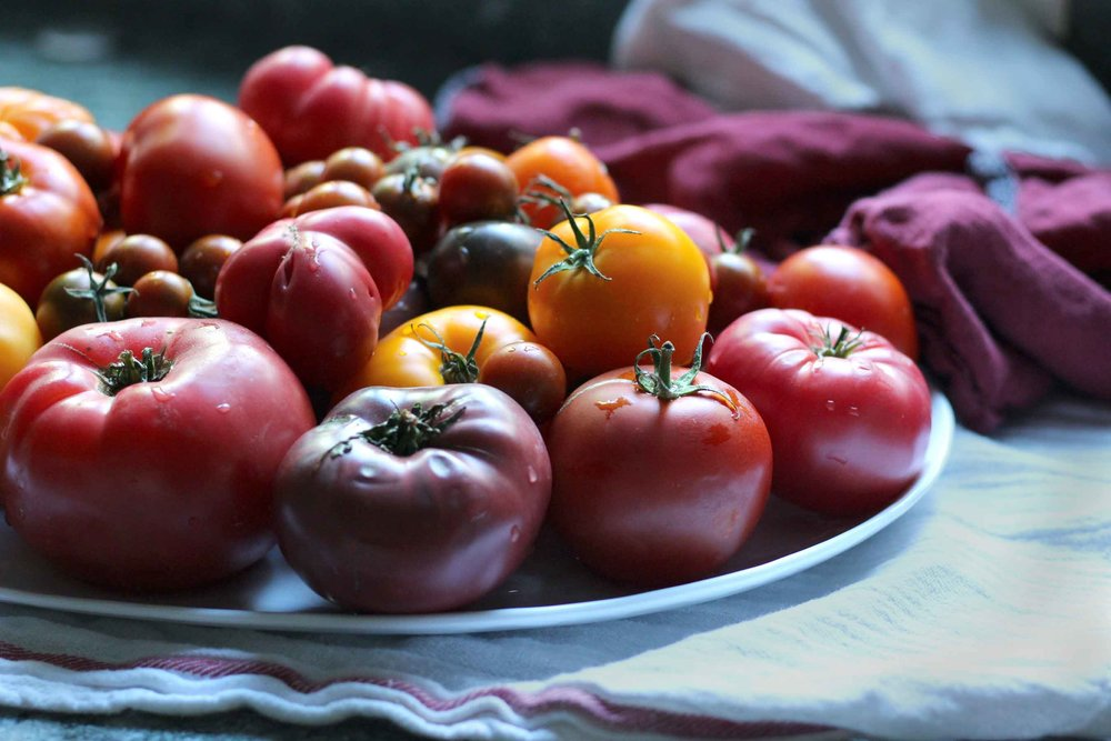 A platter of heirloom tomatoes awaits being turned into a simple, yet beautiful tomato sauce.  Enjoy it now, or freeze some fresh heirloom flavor for those dark winter months.