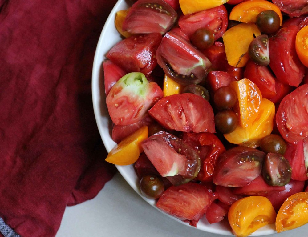 A bowl of quartered and halved heirloom tomatoes awaits being turned into tomato sauce.  Preparing to savor heirloom tomatoes during the winter months is a brilliant and simple task.