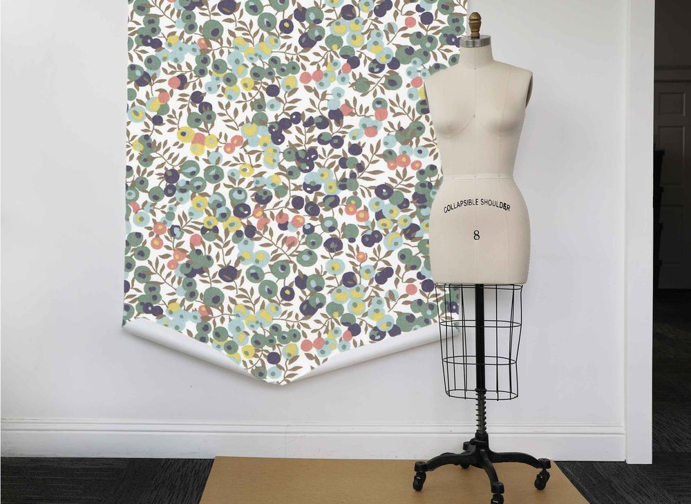 A dress form stands in front of a large print of Liberty of London's Wiltshire berry and leaf print. Thread & Whisk uses Liberty Tana Lawn with this print to trim their Bloom Culinary Totes.