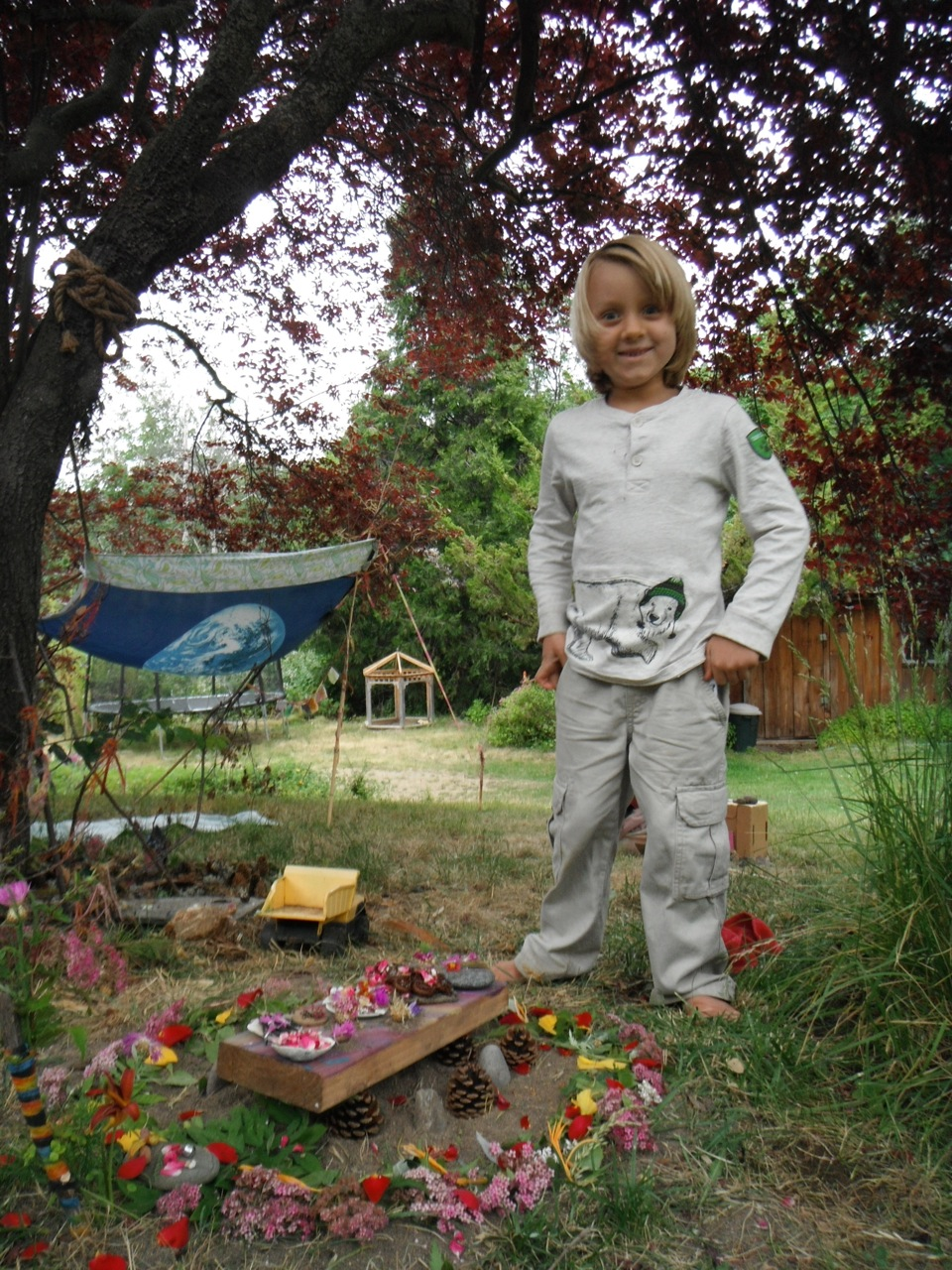 Paz age 4, with a Fairy Feast prepared by us, outside our Mother Earth Flag fort, 2014