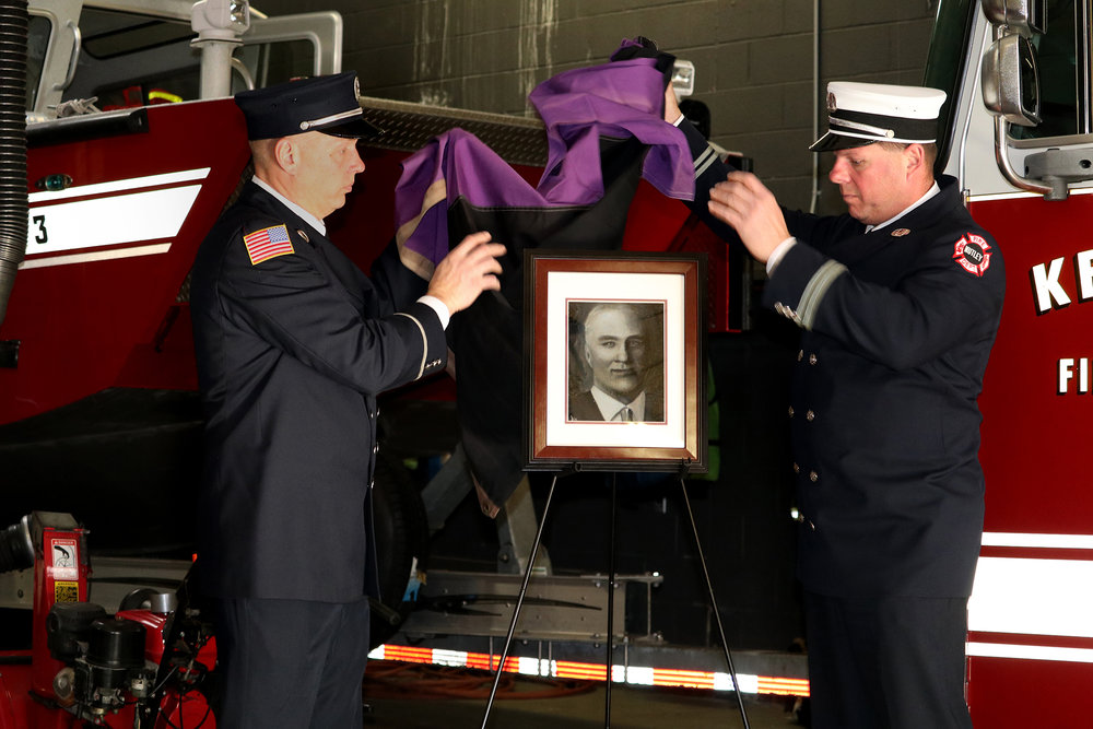 Descendants of Firefighter Robert Hamilton unveil Jen Bissu's oil portrait of him at the ceremony.