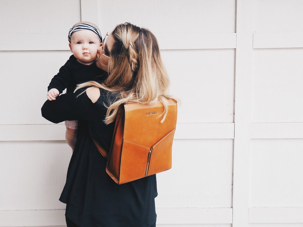 Me and my 7 month old Bella. Wearing a leather backpack from our online store!
