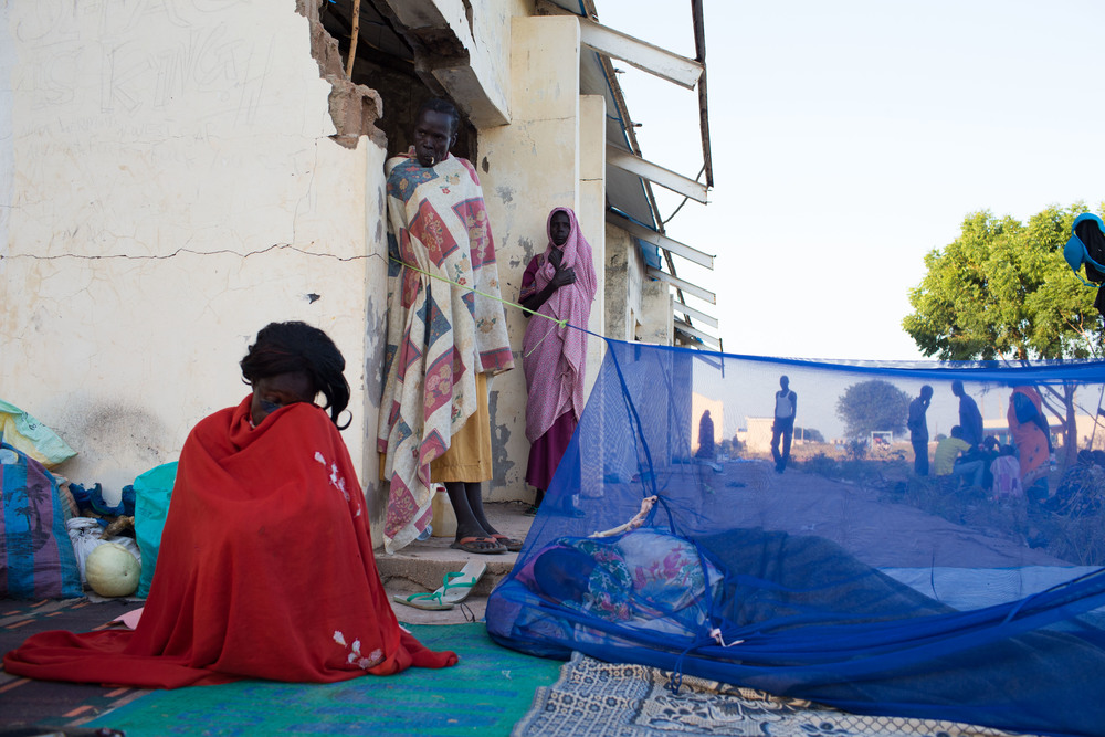 Women stay wrapped in blankets to keep warm in the early hours of the morning in Abyei.
