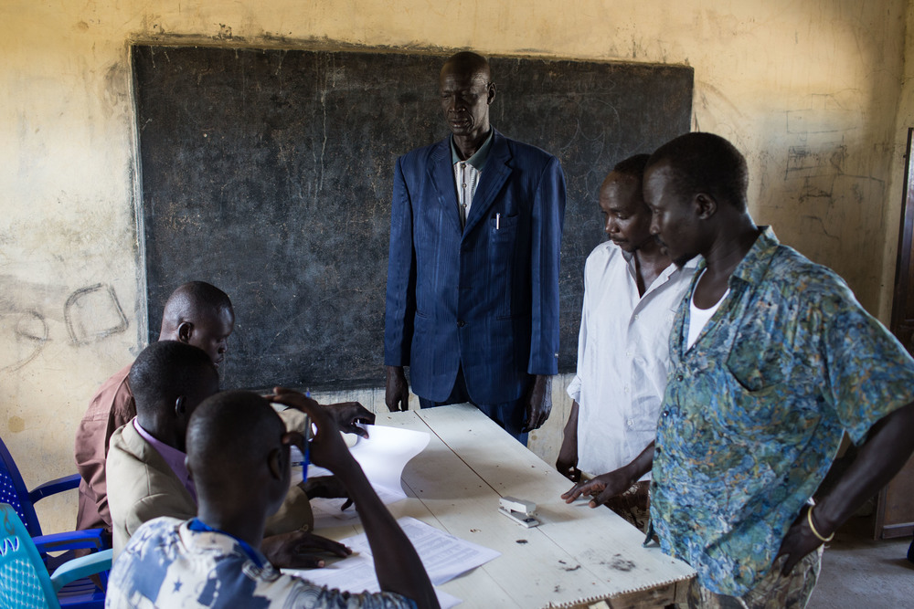 Men check their names on the registration list in an abondened school converted into a voting center in Abyei.