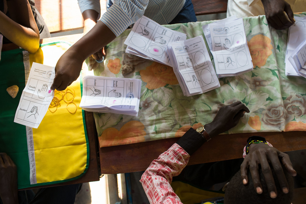 A volunteer with the AACRC holds his head while he and other volunteers count votes in Abyei.