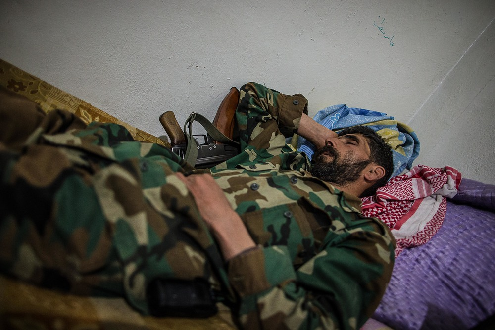 "Abu Staif, 39, naps with his gun. He was a mason before the war and if given the choice, he says he would rather die a martyr in the war than return to his old life, ""Everyone dies at some point. If I return to my old life I will still die, but to be able to be a martyr and die in a holy way is a privilege."" He is married and has eight children."