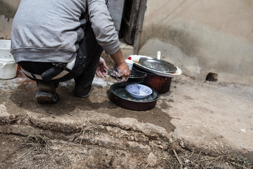 "A rebel washes dishes after lunch. ""Inside we are like wives, outside we are like Arnold,"" jokes the battalion's commander, Abu Abdo, referring to Arnold Schwarzenegger."