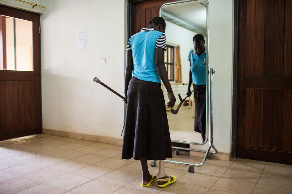 A young woman inspects her prosthetic leg in front of a mirror.