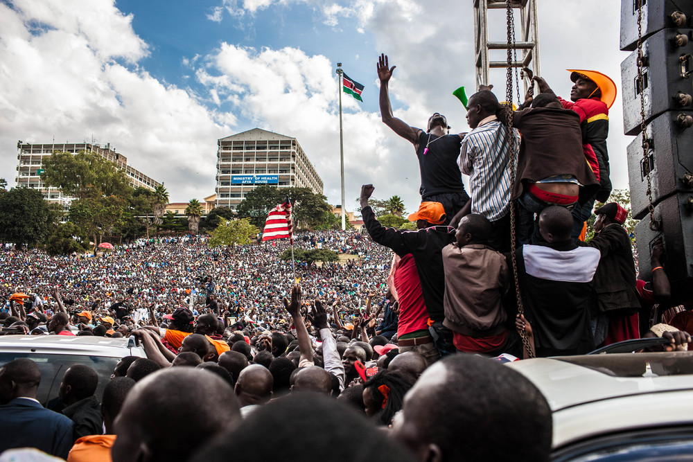 "CORD supporters swarm lighting scaffolding near the stage. ""Uhuru must go,"" run the chants."