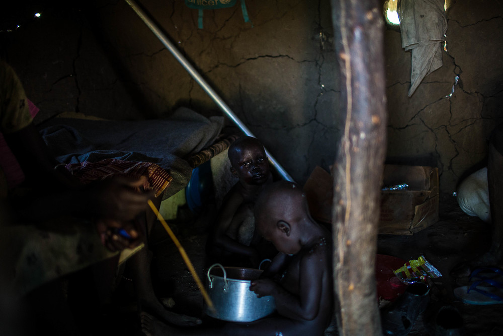 A young boy who had come from hiding in the forest that day scrapes the last bit of food from a pot while his brother looks on in their relative's home in Gumuruk, Jonglei State, South Sudan.
