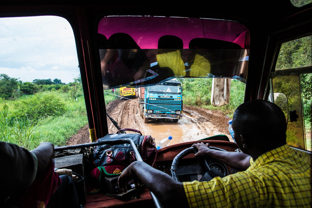 The bus navigates the muddy ruts of the road after crossing the border into Uganda. The road is frequently washed out during the rainy season.