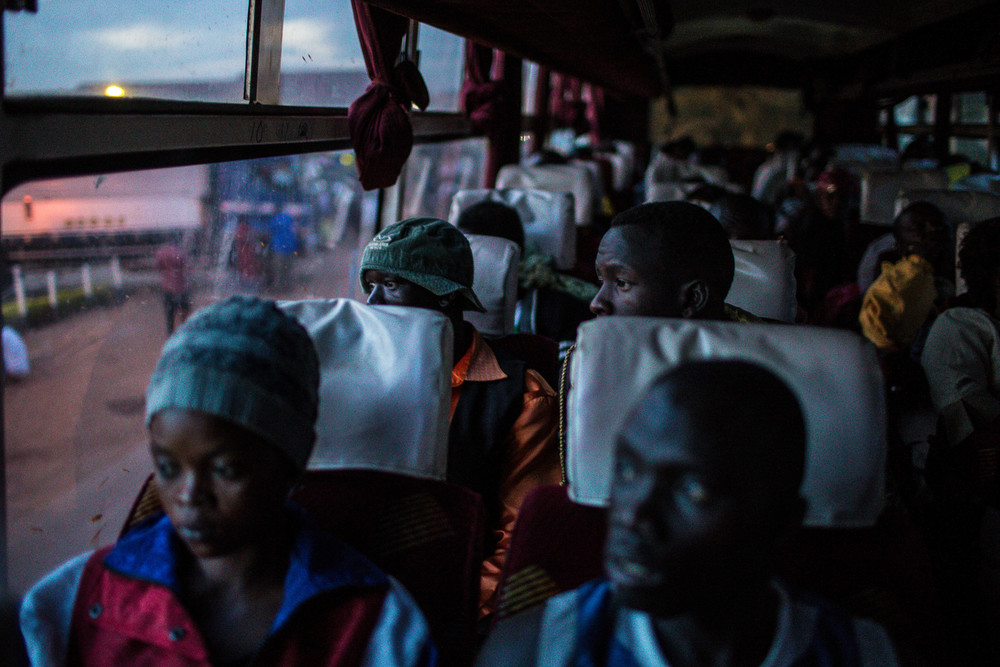 Abayok (back right) and Atak Atak peer out the window as the bus descends into Kampala.