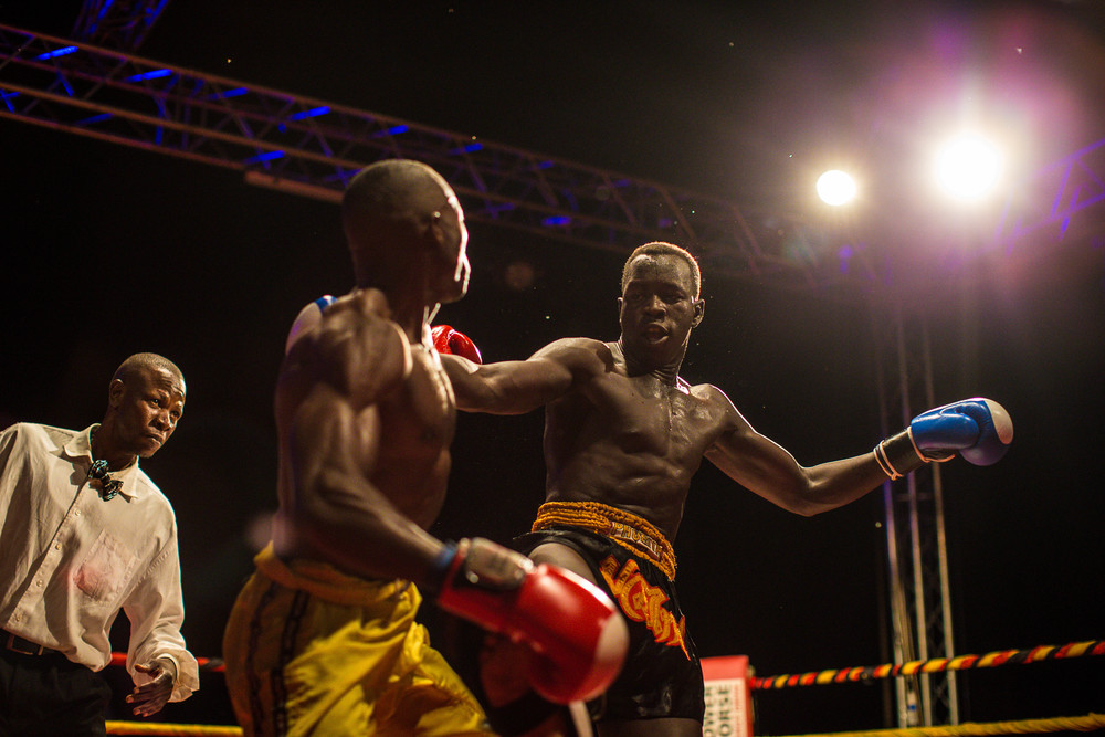A referee looks on as Abayok and his Ugandan opponent fight.