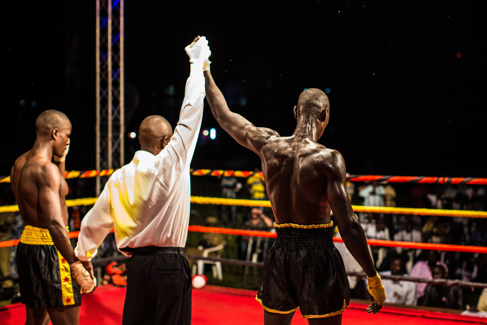 Kuol's hand is raised in victory at the end of his fight. Kuol won his match while Abayok and Ngong lost theirs.