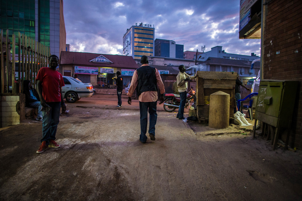 Atak Atak walks through Kampala at dawn the next morning in order to catch the bus back to Juba.