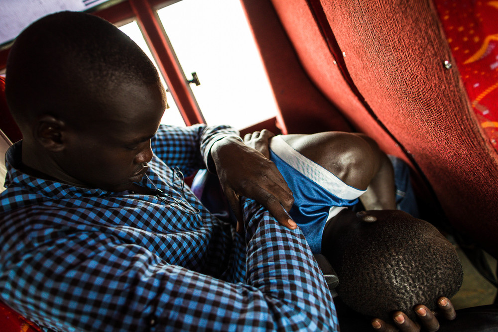 Pio sleeps on Izekal's lap as the team makes their way back to Juba.