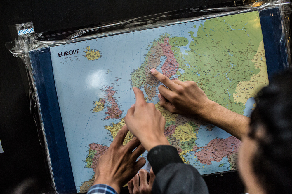Syrian refugees point to different countries on a map posted in Milano's central train station. Countries such as Sweden, Germany, and Denmark are primary destinations for Syrian refugees headed north as they see better chances there of being granted asylum quickly with relatively better financial support and social services as they try and start their new lives.