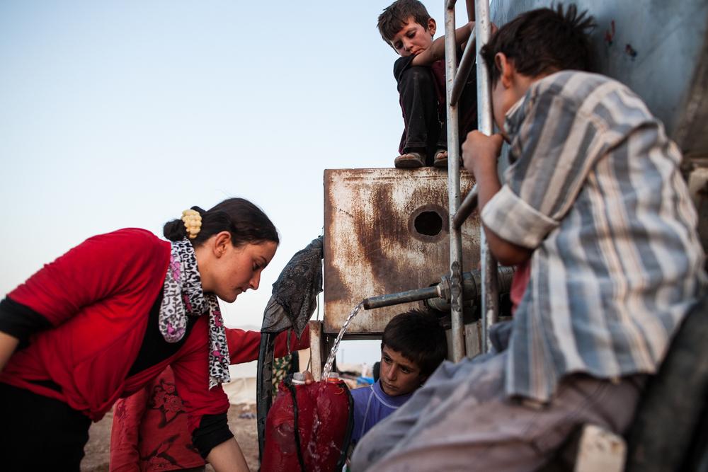 Yazidi children seeking refugee in Newroz watch as a boy fills a jerrycan of water.