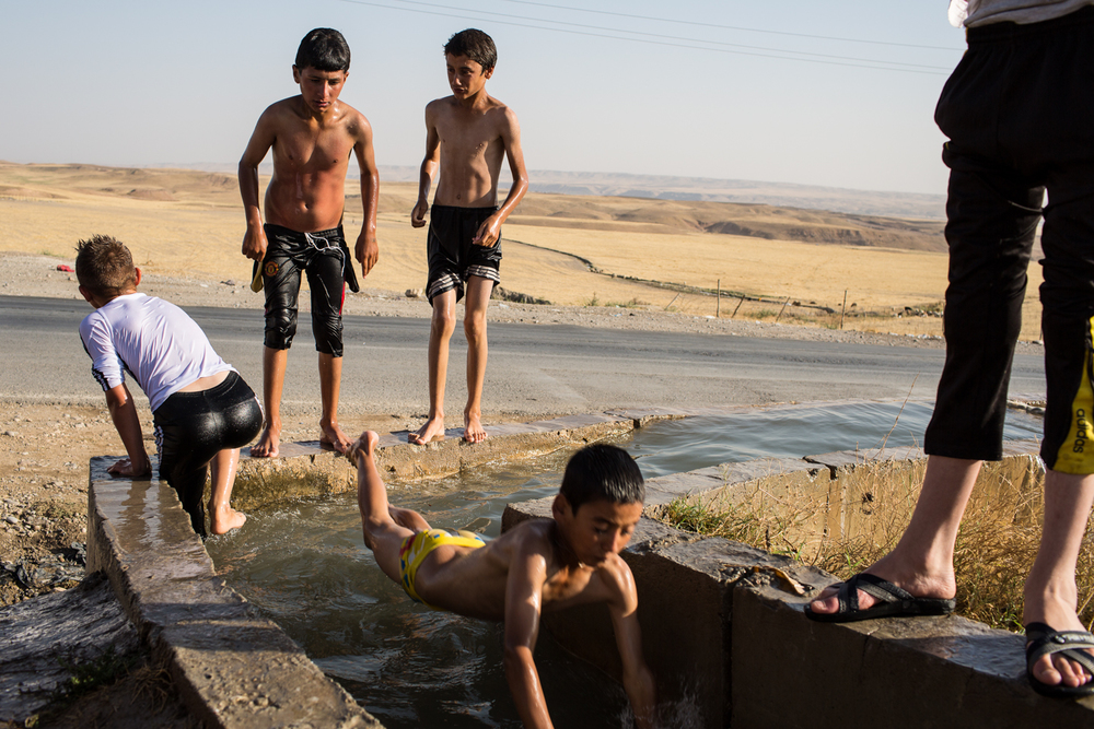 Displaced Iraqi children who have taken refuge in Peshkhabor, Iraq take a break from the searing summer heat in a channeled spring.