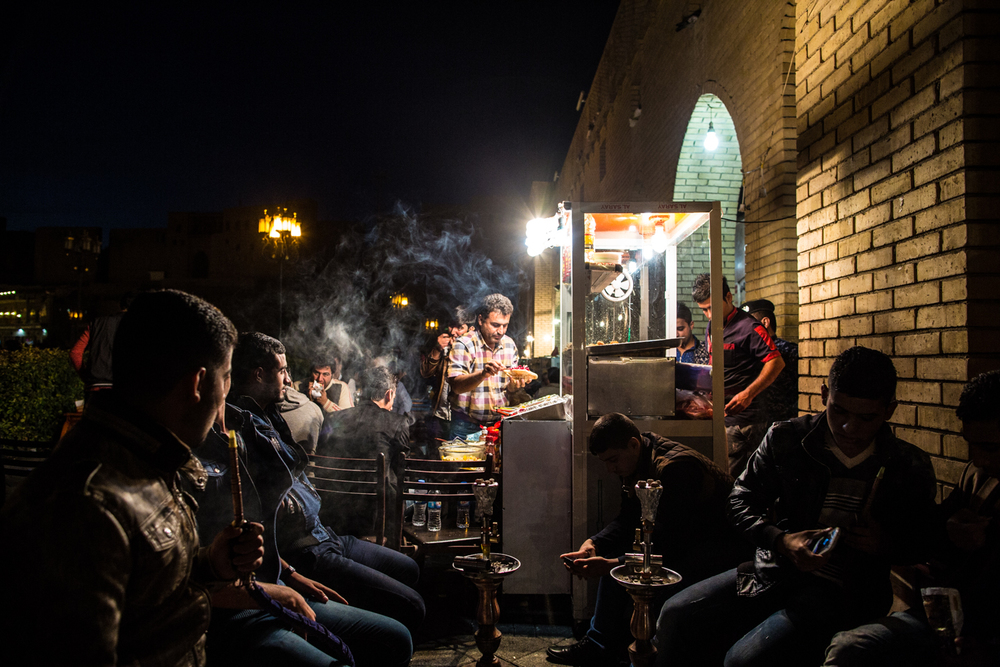 Young Kurdish men smoke water pipes as others eat at a sandwich shop in the old quarter of Erbil.