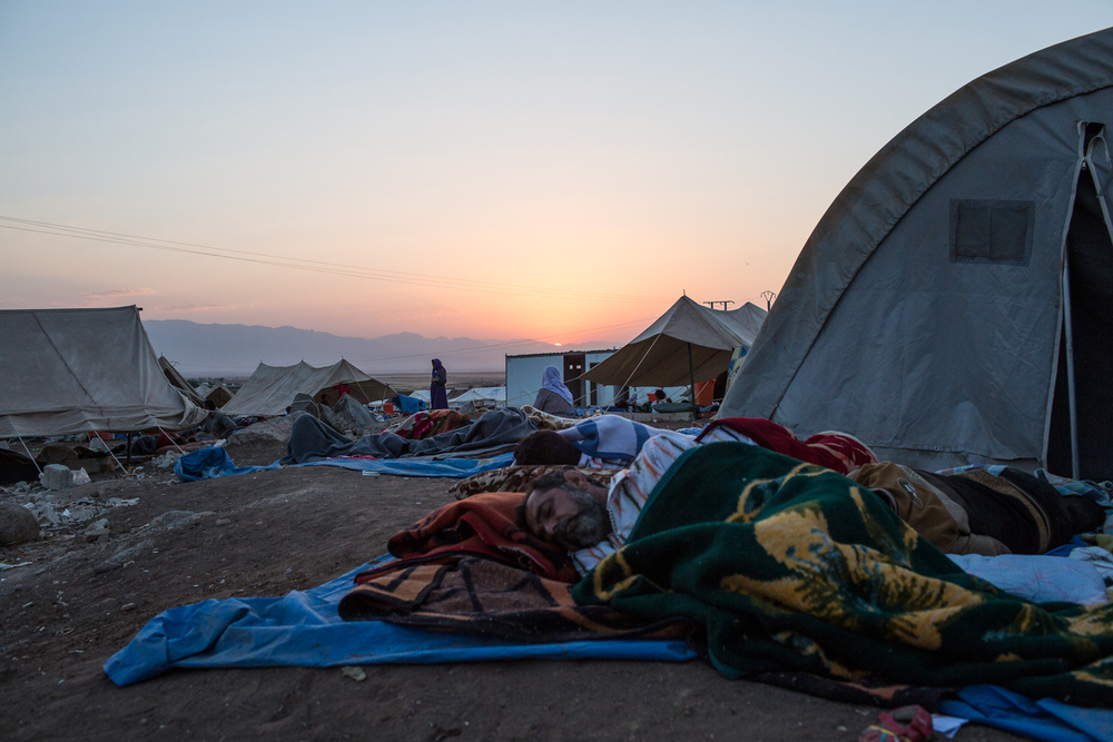 Refugees wake and rise while others sleep as the sun slides from behind a distant range of mountains in northeastern Syria.