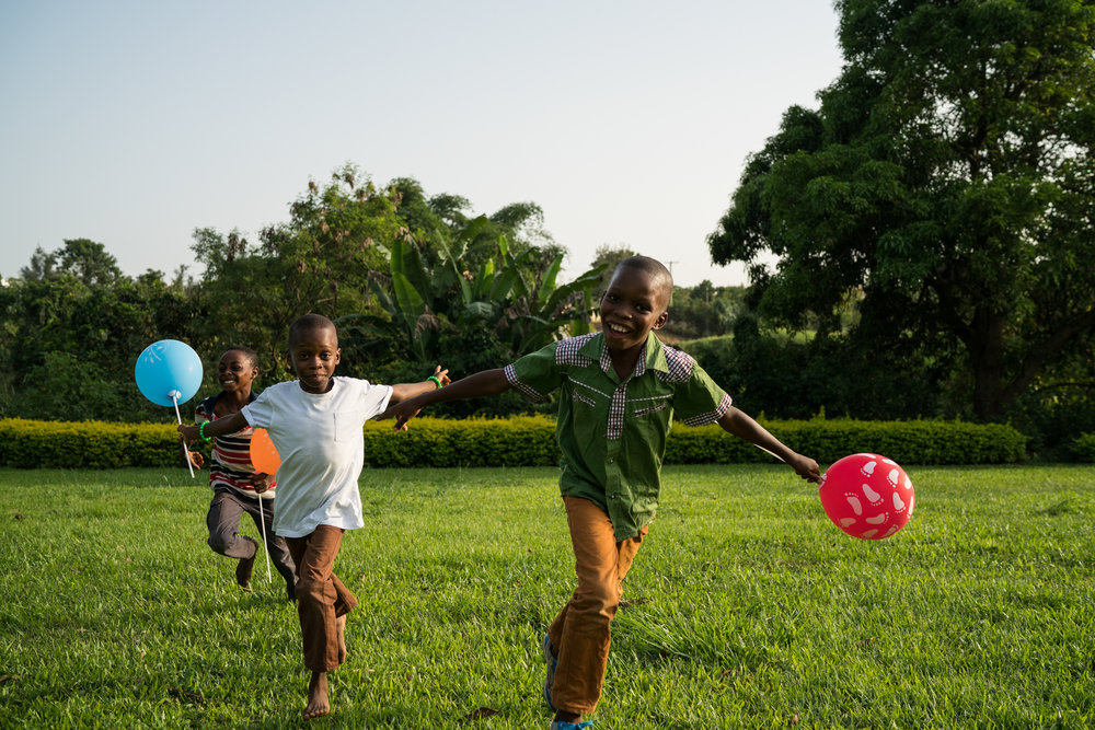 Children run through the grass at Millennium Park in Abuja.