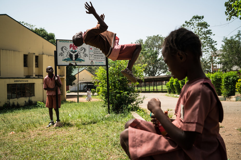 A young boy does a backflip outside of class at Festival Road Primary School in Abuja.