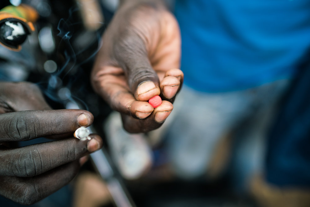 A moto-taxi driver holds a 225 mg tramadol pill in Garoua, Cameroon.