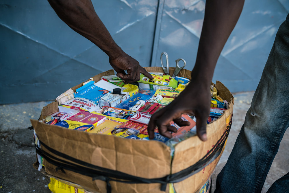 Men point to medicine they want from a box of medicine a seller carries around in Garoua, Cameroon. Mobile medicine sellers are ubiquitous in the country and sell everything from tramadol to knock-off antibiotics.