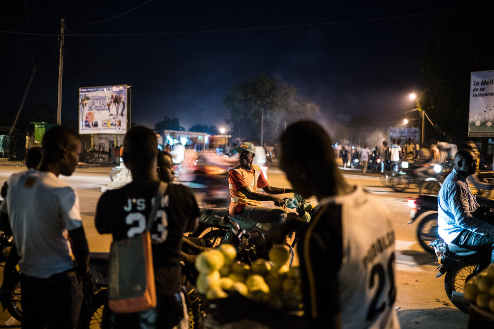 A moto-taxi driver waits for a client as others rush through a night market in Garoua, Cameroon.