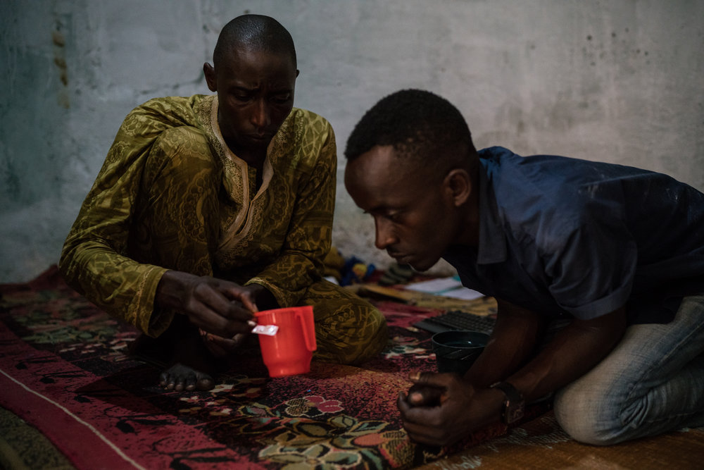 A young man named Hamid mixes tramadol in a cup as his friend, Oumarou Aziz, waits in Ngaoundere, Cameroon.