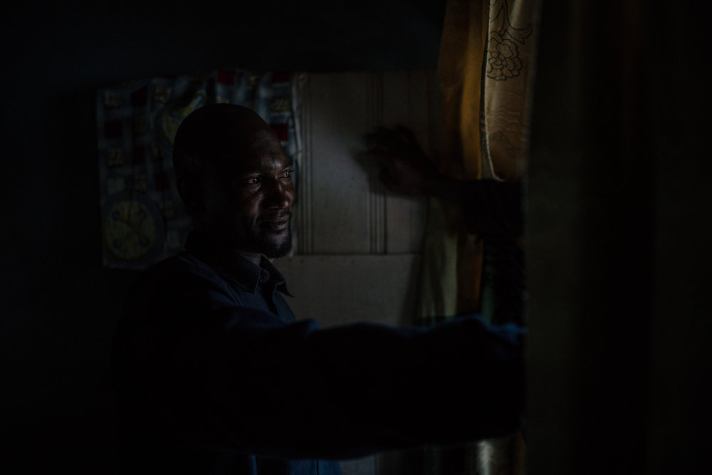 """Ibrahim, 36, who began taking the drug daily in order to help him work better, reaches through a doorway as he speaks with someone at his home in Ngaoundere, Cameroon. As his time on the drug has increased so has his dependency, saying it feels """"like all your stomach is boiling"""" when he misses a dose."""