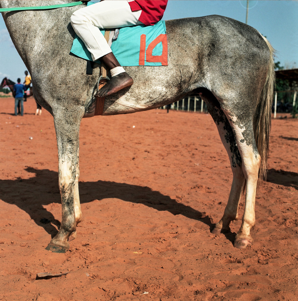 A jockey races in barefeet to save weight.