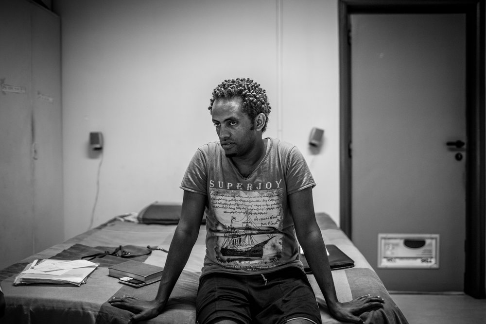Alem, 30, sits on the bed in the small room he now calls home in downtown Rome. Like thousands of his countrymen, he fled a lifetime of military service and a dictatorial government in his home of Eritrea.