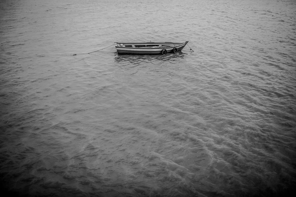 "A small fishing boat bobs in the ocean. ""I don't know what to do now,"" says Mahamadou, ""there's no work in Morocco. There's nothing here. I can't stay here, but I don't know where to go now."""