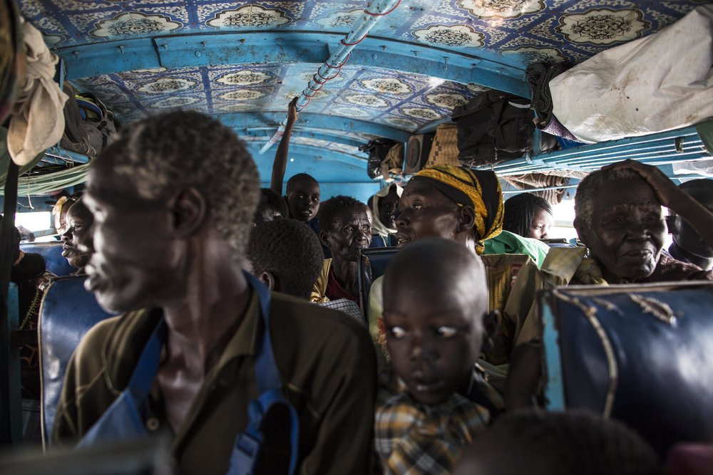 Passengers look out the windows as the bus departs Malakal.