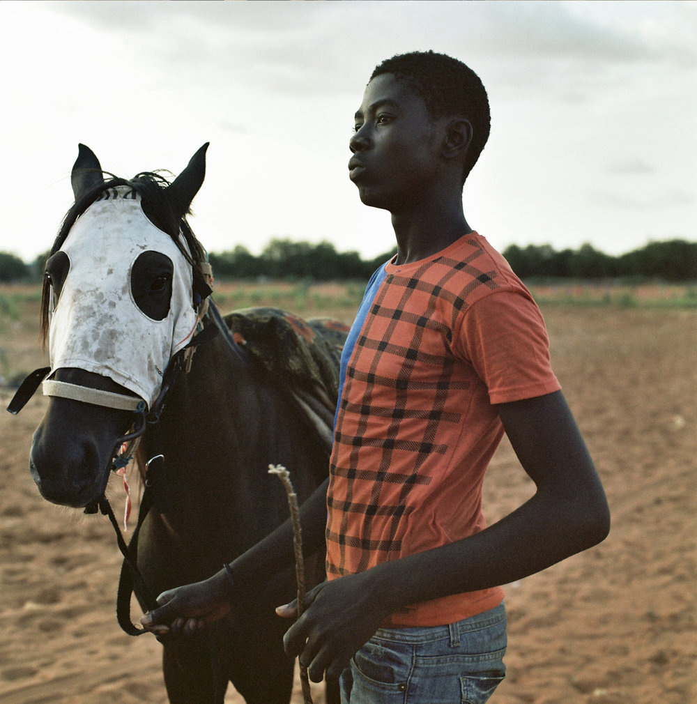 Osman, 16, waist with a horse he's been prepping for a race. He's been riding since he was nine.
