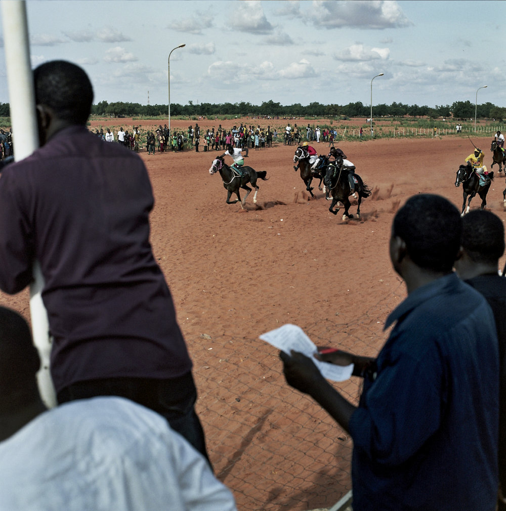 Horses and jockeys race down the final stretch as bystanders look on.