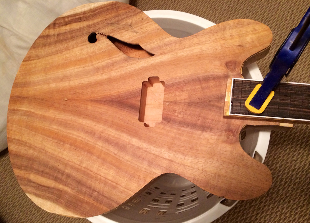 Koa top glued on and sound holes started.